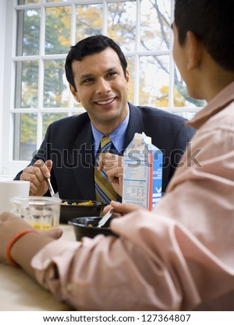 Father and his teenage son having breakfast together