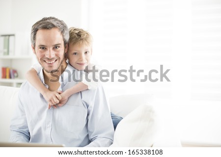 Father and his young son smiling and look the camera