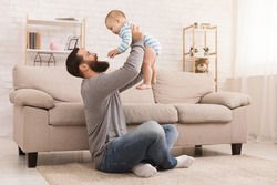 Father and kid spending time together, man throwing up his son at home in living room, copy space