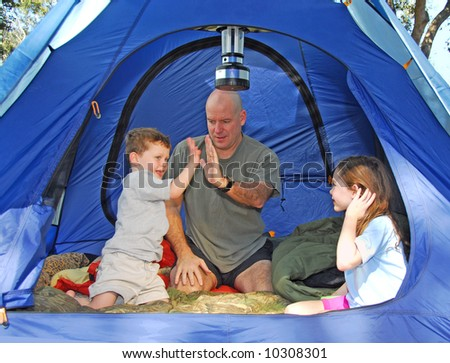 Father and Kids outdoors camping in dome tent - stock photo
