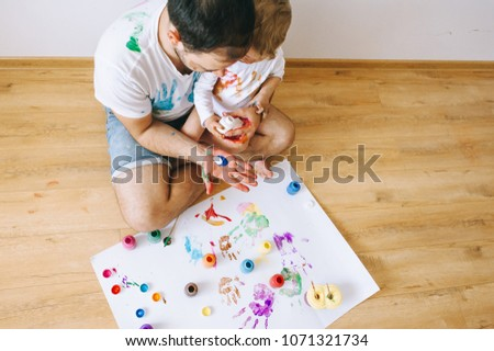 Father and little boy of fivr years having fun painting at home #1071321734