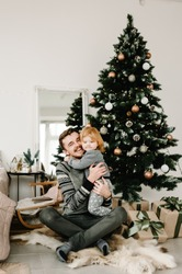 Father and little child having fun and playing together at home. Portrait loving family close up. Cheerful dad hugging cute baby daughter girl near Christmas tree. Merry Christmas and Happy Holidays.
