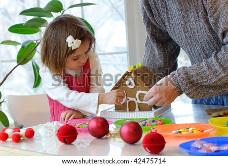 Father and little daughter assembling a gingerbread house