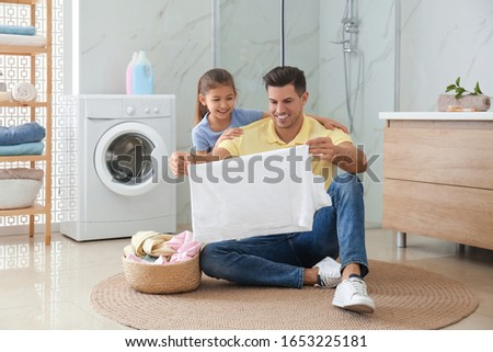 Father and little daughter with clean laundry in bathroom