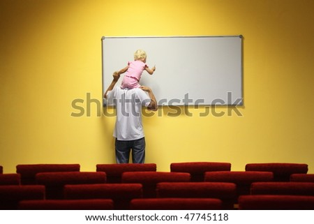 father and little girl in empty presentation hall. little girl is sitting on a father's neck. chair in out of focus.
