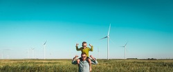 Father and little kid having fun and play together in wind turbine field. child boy shows power while riding on father's shoulders. instagram vintage color filter.