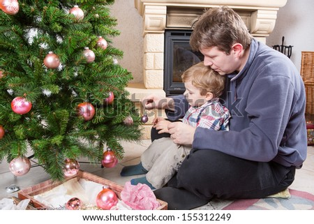 Father and little son decorating christmas tree at home with chimney
