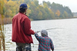 Father and little son fishing together on autumn day outdoors background