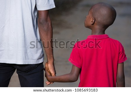 father and little son holding hands walking on a road. the father's hand lead his son into the wild with confidence in the outdoors protecting him.the parental concept of parental care. road to life. #1085693183