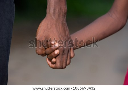 father and little son holding hands walking on a road. the father's hand lead his son into the wild with confidence in the outdoors protecting him.the parental concept of parental care. road to life. #1085693432