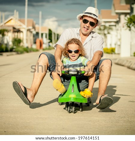 father and little son playing near a house at the day time