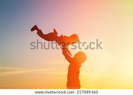 father and little son silhouettes play at sunset sky