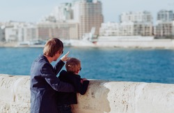 father and little son travel in the city looking at modern buildings