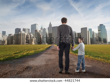 father and little son walking on a country road towards a modern city - stock photo