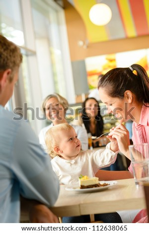 Father and mother feeding child cake cafe woman man eating