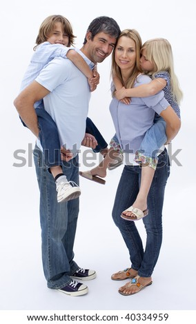 Father and mother giving boy and girl piggy back ride against white background
