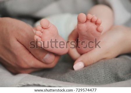 father and mother holding babies feet