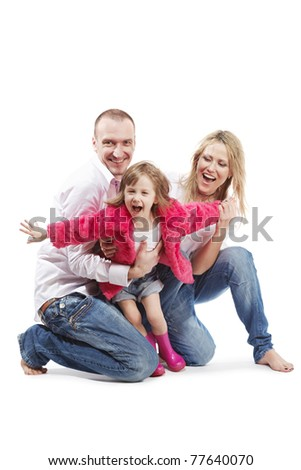 Father and mother in the white shirts and blue jeans barefooted and little daughter in the pink gumboots and fur jacket with outstretched arms as if she trying to fly.