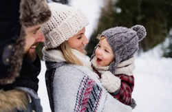 Father and mother with small child in winter nature, standing in the snow.