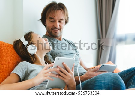 Father and pre teen daughter playing on tablet together on couch in room at home. Good parent and child relations.