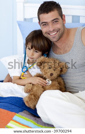 Father and sick son playing doctors in bed with a teddy bear