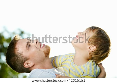 Father and small little son in embraces look in the sky