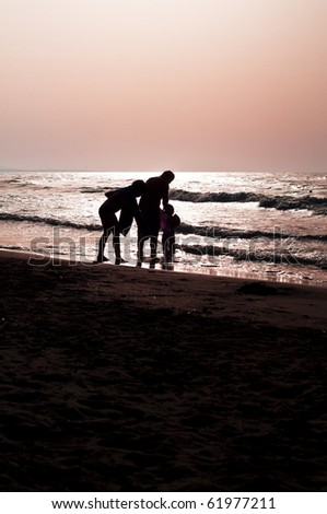 father and son against the sea on the beach at sunset
