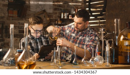Father and son are making chemistry experiments while checking a tablet computer in a garage at home.