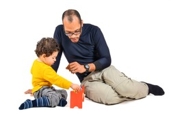Father and son are playing together as part of the didactic children therapy. A therapist is working with little child. Didactic therapeutic toys for autism.