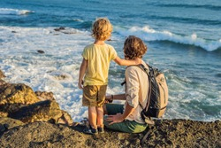 Father and son are walking along the cosmic Bali beach.. Portrait travel tourists - dad with kids. Positive human emotions, active lifestyles. Happy young family on sea beach.