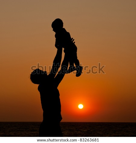father and son at sunset sea