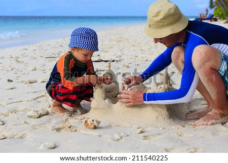 father and son building sand castle on tropical sand beach