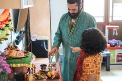 Father and son celebrating Diwali or hindu festival at home - Focus on man face