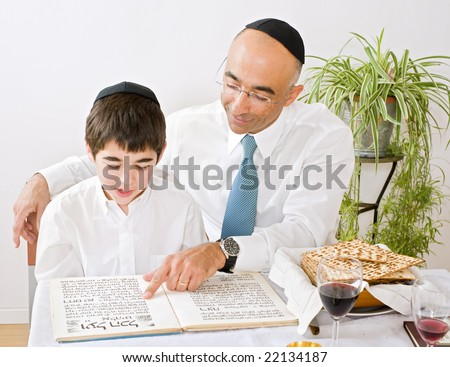 father and son celebrating passover reading the Hagada - stock photo