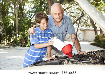 Father and son changing the motor oil in the family car.