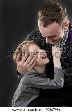 Father and son cheerfully talk. On a gray background. Boy not in focus.