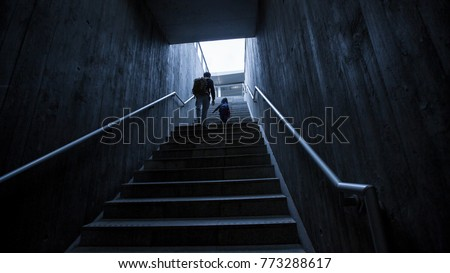 father and son climbing stairs in pedestrian subway, going to the city. Concept of family in town #773288617