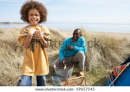 Father And Son Collecting Firewood On Beach Camping Holiday