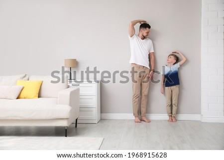 Father and son comparing their heights near wall in living room Foto stock ©