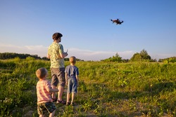 Father and son controls RC drone quadrocopter in the sky
