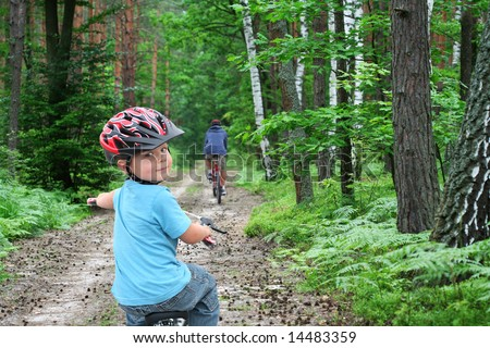 Father and son cycling on a green forest path