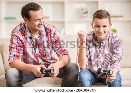 Father and son dressed casual having fun at home while playing computer games.