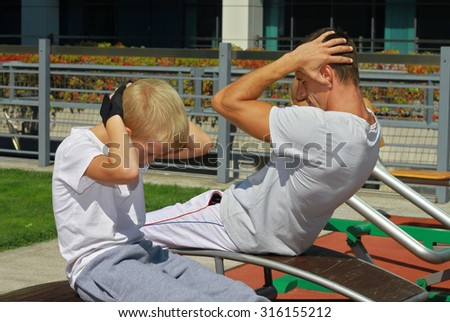 Father and son during street workout in outdoor gym. Strong man and little boy. Family, sport, fitness, active lifestyle concept
