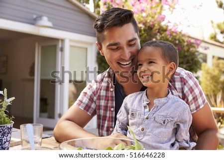 Father And Son Eating Outdoor Meal In Garden Together #516646228