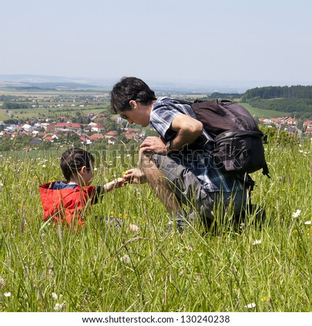 Father and son,exploring the nature on a countryside meadow in summer, village in the background.