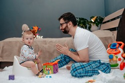 Father and son. Father teaches a child to walk on a potty. Father does begs and asks. The child is playing. Baby toiletries. Potty training.