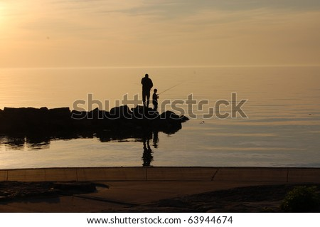 Father and son fish off pier on a summer evening/Evening Fishing/ Finding time together