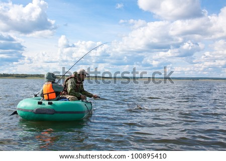 Father and son fishing at boat