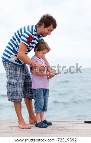 Father and son fishing from pier caught fish