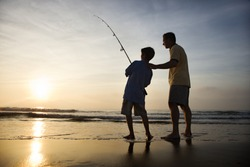 Father and son fishing in ocean surf at sunset.